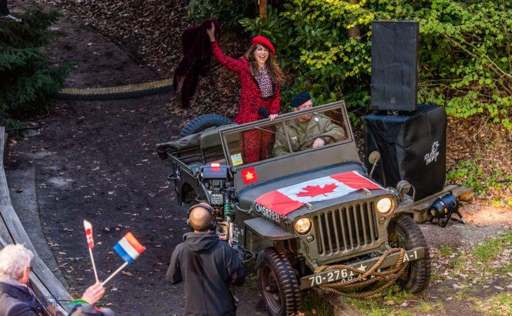 Ellen ten Damme in een authentieke leger-jeep met Canadese vlag op de motorkap.